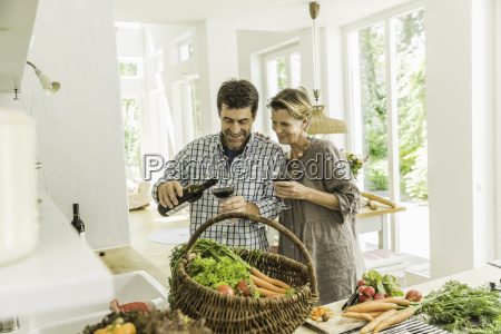 couple pouring red wine whilst preparing