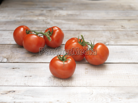 six red vine tomatoes on wooden