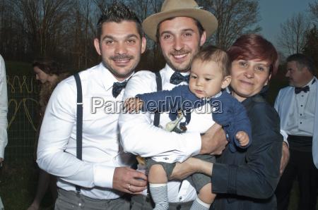 portrait of groom holding baby boy