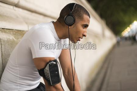 exhausted male runner wearing headphones taking