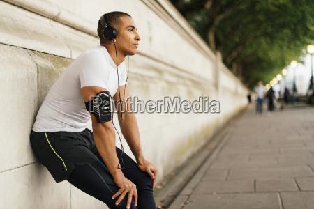 male runner wearing headphones taking a