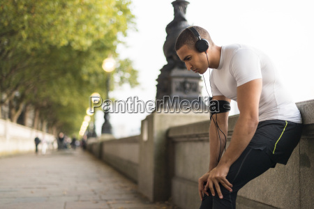 young male runner wearing headphones taking