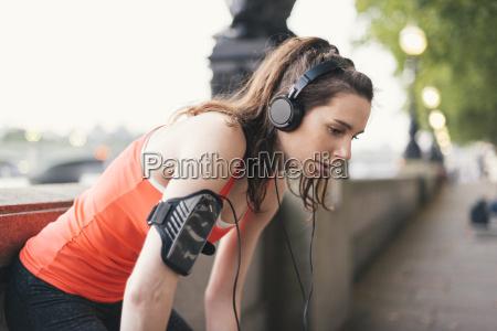 exhausted female runner wearing headphones taking