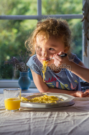 girl eating plate of pasta at