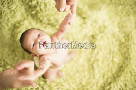 father holding baby girls hands high