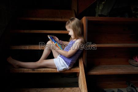 little girl sitting on basement steps