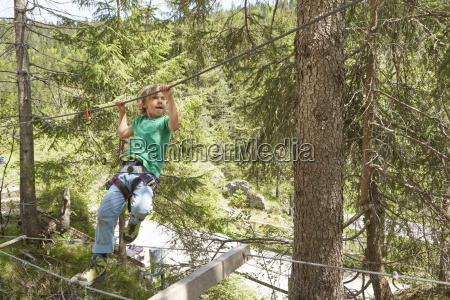 boy moving along rope in forest