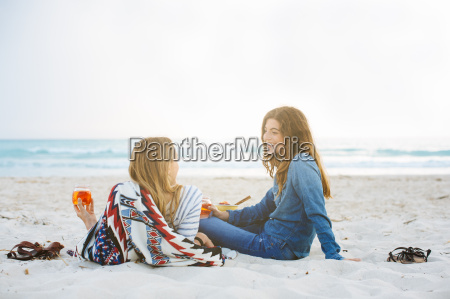 two young female friends reclining with