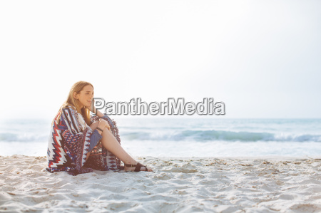 young woman wrapped in blanket sitting
