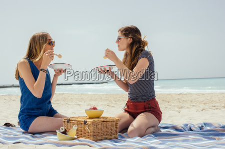 two young female friends eating picnic
