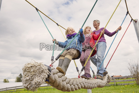 grandmother and grandchildren playing on rope