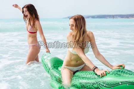 two young female friends wearing bikinis