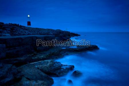 lighthouse overlooking rocky beach