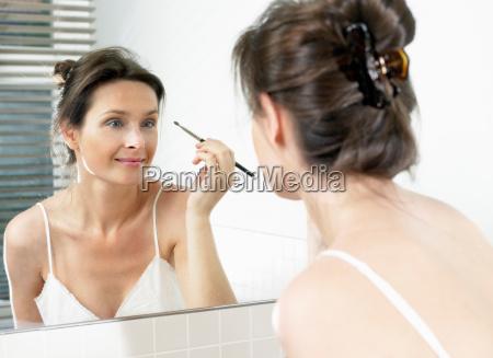 woman in bathroom applying makeup
