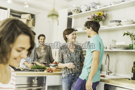 five adult friends chatting and preparing