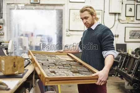 young man carrying letterpress tray in