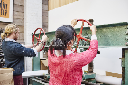 man and woman turning print press