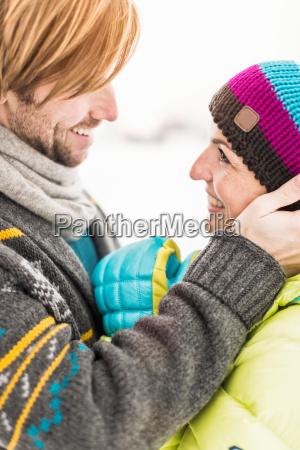 man touching womans face woman wearing