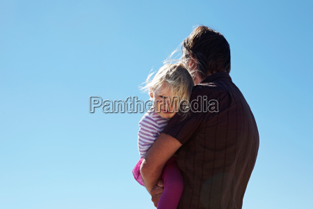 mature man holding daughter in arms