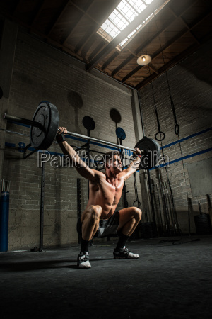 young man squatting and lifting barbell