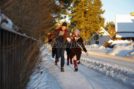 teenagers running on icy sidewalk