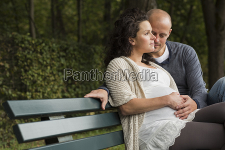 pregnant couple caressing belly on park
