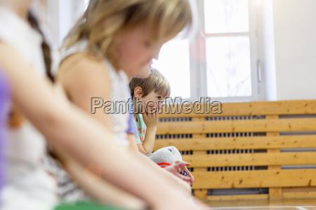 children sitting on bench in school