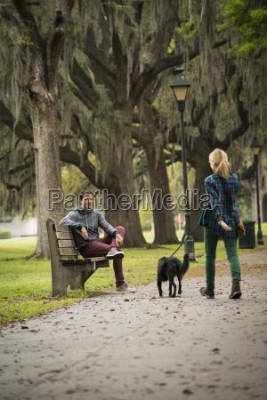 man on park bench woman walking