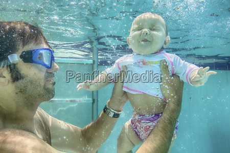 father holding baby daughter underwater
