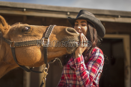 cowgirl showing affection to horse on