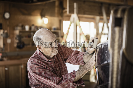 senior man working on boat building