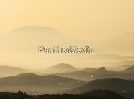 silhouetted misty valley at sunset sardinia