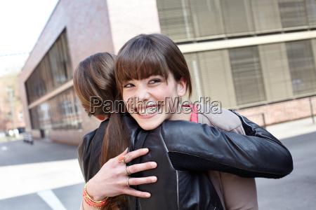 smiling women hugging on city street