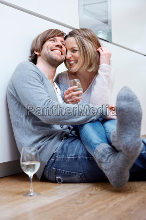 couple sitting on kitchen floor with