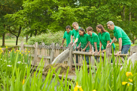 gardeners peering over fence in park
