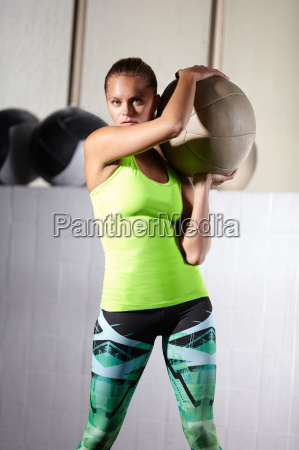 portrait of young female crossfitter holding