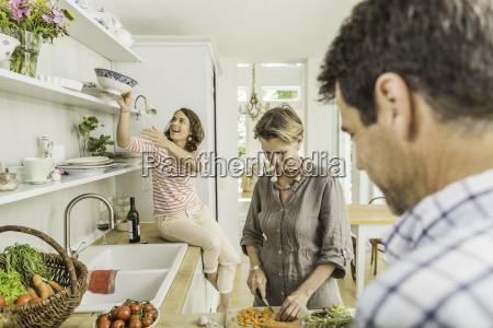 three adults preparing fresh vegetables in