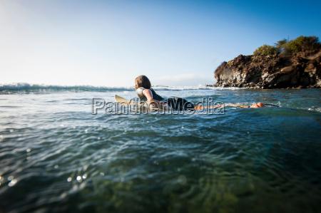 surfer paddling in ocean