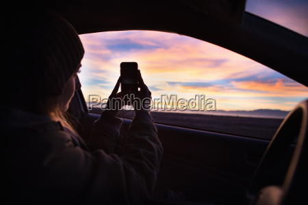 young woman taking photograph of sunset