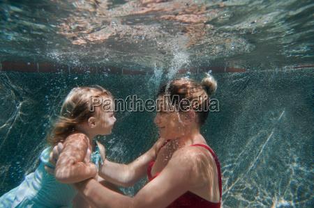 underwater shot of mother holding daughter