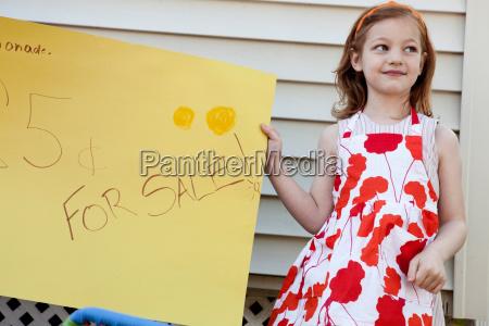 girl holding homemade lemonade for sale