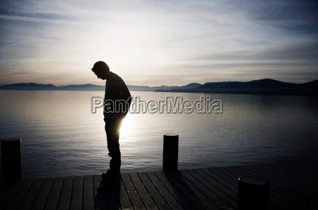 man standing on pier at sunset