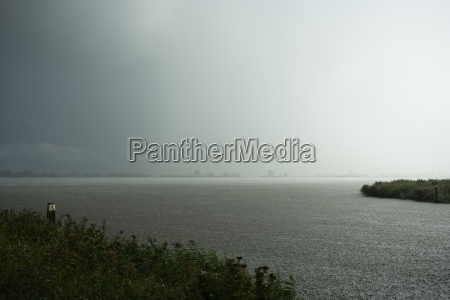 heavy rainfall over lake during thunderstorm