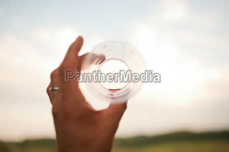 womans hand holding empty drinking glass