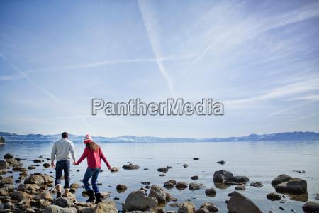 couple walking on rocks near lake