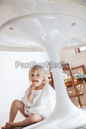 girl eating cookie under table