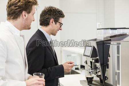 man wearing business attire getting drink