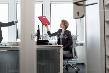 businesswoman handing file to man in