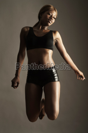 studio shot of woman jumping mid