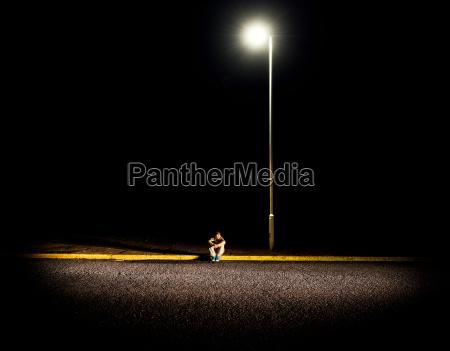 boy sitting on pavement at night